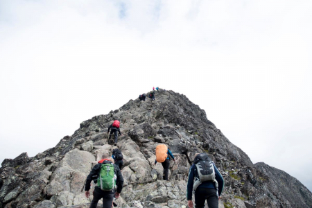 A photo of 5 people in backpacking gear walking up a mountainside.