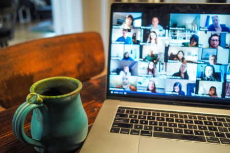 Computer with digtal meeting next to a cup of coffee on a wooden table